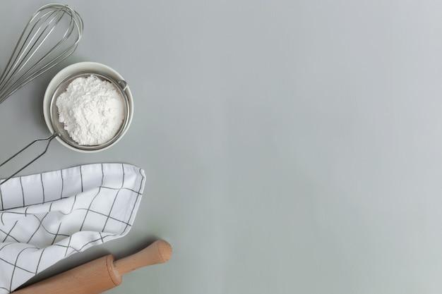 Ingredientes de panificação, utensílios de cozinha, conceito de cozinha em plano de fundo cinza leigo, copie o espaço. prepare a massa, tigela de farinha, rolo, bata, pano de prato, sal, refrigerante, peneira. foto na mesa da cozinha