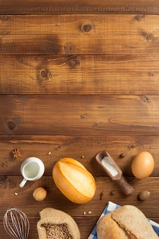 Ingredientes de pão e panificação no fundo da mesa de madeira, vista superior