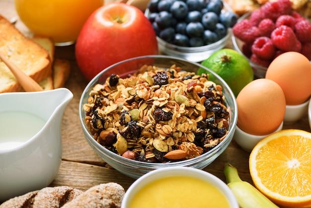 Ingredientes de pequeno-almoço saudável, quadro de comida. granola, ovos, nozes, frutas, bagas, torradas, leite, iogurte, suco de laranja, queijo, banana, maçã