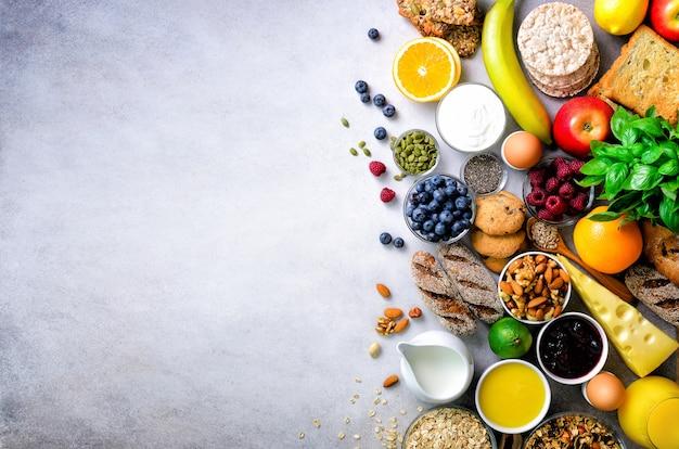 Ingredientes de pequeno-almoço saudável, quadro de comida. granola, ovos, nozes, frutas, bagas, torradas, leite, iogurte