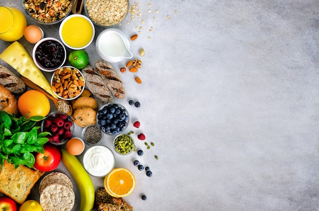 Ingredientes de pequeno-almoço saudável, quadro de comida. granola, ovos, nozes, frutas, bagas, torradas, leite