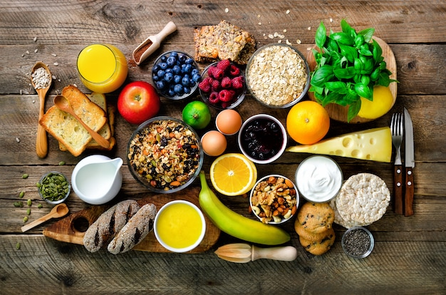 Ingredientes de pequeno-almoço saudável, quadro de comida. granola, ovos, nozes, frutas, frutas vermelhas, torradas, leite, iogurte, suco de laranja