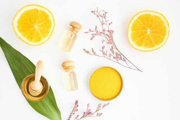 Ingredientes de produtos de cuidados da pele. e o mel no copo, pacote de etiqueta em branco para maquete no fundo branco e nas flores. o conceito de produtos de beleza natural.