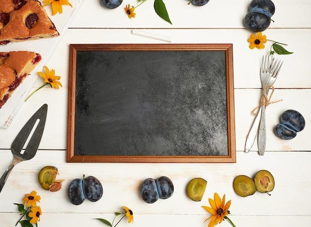 Ingredientes de quadro preto giz vazio e fatias de bolo de ameixa
