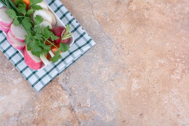 Ingredientes de salada fresca empacotados em uma bandeja sobre uma toalha dobrada na superfície de mármore