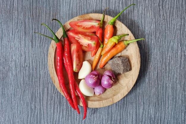 Ingredientes de sambal quente e picante, colocados na placa de madeira na mesa de madeira preta