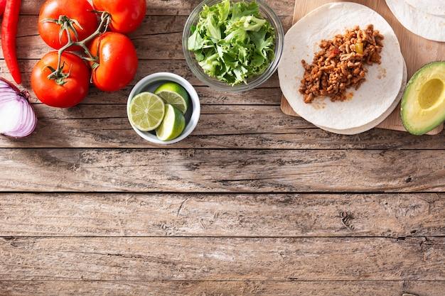 Ingredientes de tacos mexicanos em mesa de madeira
