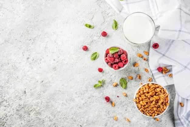 Ingredientes do café da manhã saudável. cereais de pequeno-almoço, copo de leite ou iogurte, framboesas
