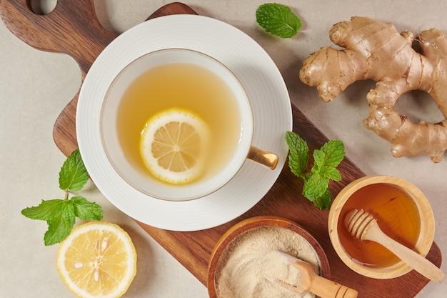 Ingredientes do chá de gengibre, chá reconfortante e aquecedor saudável sob receita simples. chá de gengibre e ingredientes - limão, mel. vista superior. postura plana. recém-saído do jardim orgânico de crescimento doméstico. conceito de comida.