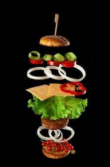 Ingredientes do cheeseburger levitando: costeleta de carne suculenta, queijo, pão de gergelim, alface, anéis de cebola branca, fatia de tomate, pepino em fundo preto. fast food flutuando no ar