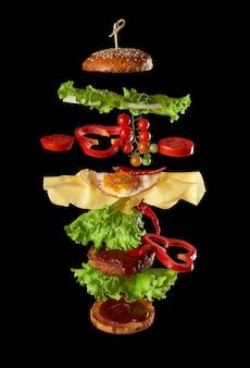 Ingredientes do cheeseburguer voador: costeleta de carne, pão de gergelim, queijo, ovo frito, tomate e alface verde em fundo preto