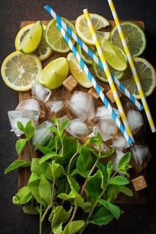 Ingredientes do coquetel de mojito, hortelã fresca, limão, limão, açúcar, gelo em uma mesa escura. vista superior.