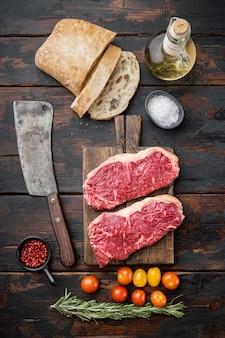 Ingredientes do hambúrguer de bife com carne, carne marmorizada, em fundo escuro de madeira, vista de cima