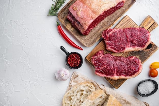 Ingredientes do hambúrguer de bife de carne crua, com carne marmorizada, em fundo branco, vista de cima, com espaço de cópia para o texto