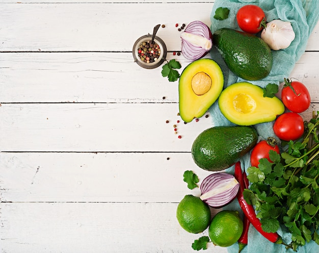 Ingredientes do molho guacamole - abacate, tomate, cebola, pimenta, alho, coentro, limão no fundo branco. vista do topo
