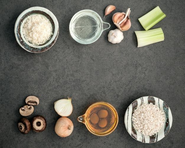 Ingredientes do risoto dos cogumelos no fundo de pedra rústico escuro com espaço liso da configuração e da cópia.