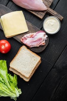 Ingredientes do sanduíche club, na mesa de madeira preta, vista superior com espaço de cópia para o texto