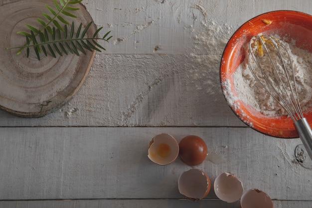 Ingredientes e ferramentas para fazer a massa, farinha, ovos e um batedor em um fundo branco de madeira.
