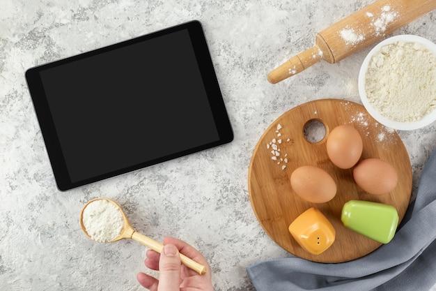Ingredientes e ferramentas para panificação e tablet com tela em branco e lugar para texto ou imagem na mesa branca.