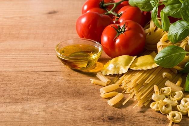 Ingredientes e massas italianas ravioli, macarrão penne, espaguete, tortellini, tomate e manjericão na mesa de madeira