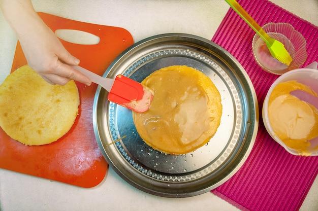 Ingredientes e utensílios de cozimento para cozinhar o bolo de esponja. processo de cozinhar pão de ló. mulher coloca o creme sobre os bolos. vista superior plana leiga