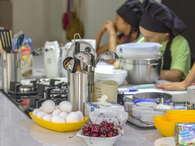 Ingredientes e utensílios de cozinha em cima da mesa. crianças-cozinheiros em segundo plano.