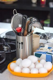 Ingredientes e utensílios de cozinha em uma tabela em um copo do metal.