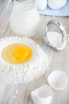 Ingredientes e utensílios para panificação - farinha, ovos e copo de leite na mesa rústica de madeira. preparação de massa caseira