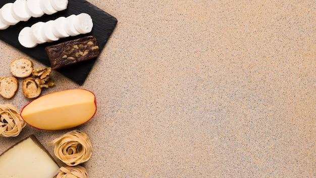 Ingredientes frescos com fatias de queijo no lado esquerdo do pano de fundo
