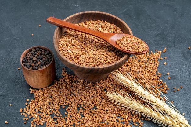 Ingredientes frescos de trigo sarraceno cru de vista frontal dentro de um prato marrom no espaço cinza