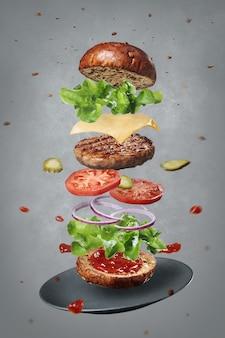 Ingredientes frescos de um delicioso hambúrguer quente levitando com um prato