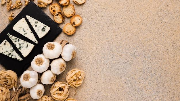 Ingredientes frescos e fatias de queijo gorgonzola na bandeja de ardósia sobre a superfície texturizada