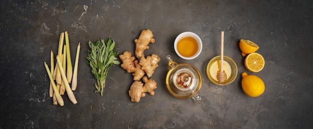 Ingredientes frescos gengibre, erva-cidreira, sálvia, mel e limão para chá de gengibre antioxidante e anti-inflamatório saudável em fundo escuro, com espaço de cópia. vista do topo.