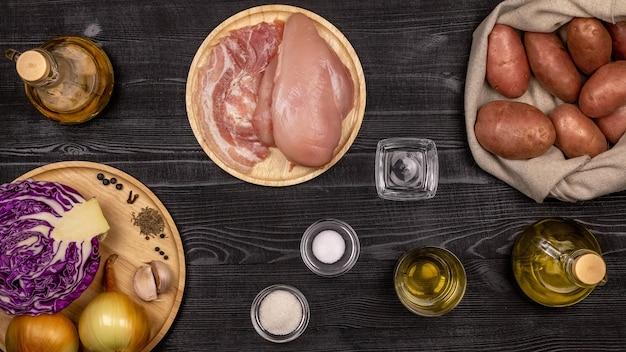 Ingredientes frescos para cozinhar batatas fritas, repolho cozido e salsichas grelhadas ou chevapchichi com base em receitas caseiras em uma mesa de madeira rústica preta. vista do topo.