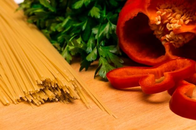 Ingredientes frescos para cozinhar: macarrão e pimentão e salsa na mesa de fundo de madeira.