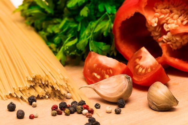 Ingredientes frescos para cozinhar: macarrão e tomate, pimentão e salsa na mesa de fundo de madeira.