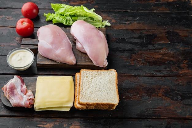 Ingredientes frescos para um sanduíche saboroso, em fundo escuro de madeira com espaço de cópia para o texto