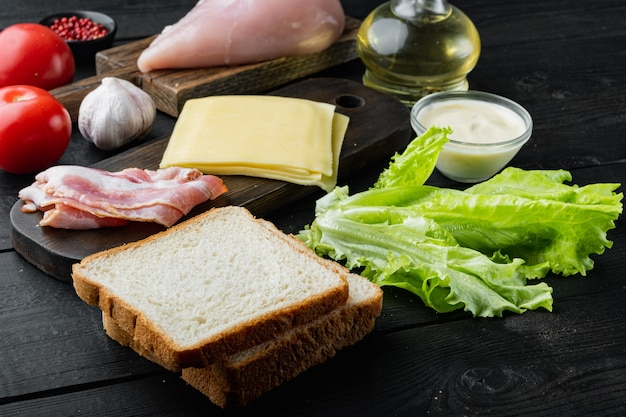 Ingredientes frescos para um sanduíche saboroso, em fundo preto de madeira