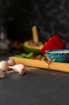 Ingredientes naturais para cozinhar macarrão, espaguete cru amarrado com uma corda, sal e pimenta nas mesas