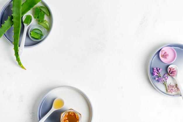 Ingredientes naturais para fazer loção caseira cosmética ou óleo essencial sobre um fundo cinza claro.