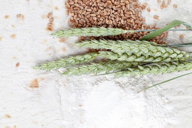 Ingredientes no pão de trigo fino, farinha, espiguetas verdes e grãos