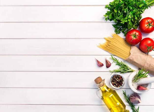 Ingredientes orgânicos frescos, macarrão espaguete de receitas italianas. conceito de comida saudável no fundo da mesa de madeira branca. vista superior, copie o espaço.