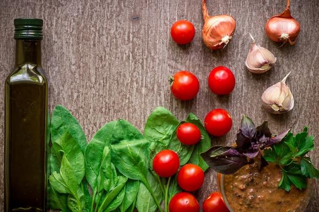 Ingredientes orgânicos frescos para fazer molho de tomate espinafre brotos de azeite de manjericão em fundo rústico.