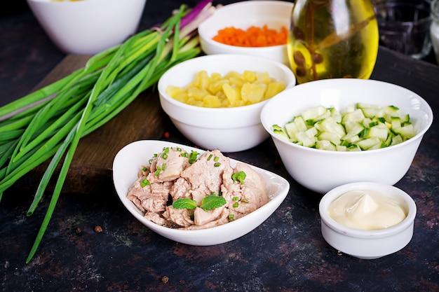 Ingredientes para a preparação de salada de fígado de bacalhau com ovos, pepinos, batatas e cenoura em um tigelas.