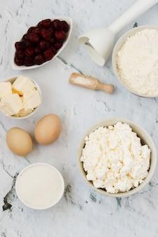 Ingredientes para a preparação do bolo com cerejas: farinha, fermento em pó, ovos, queijo cottage, manteiga, açúcar e cereja