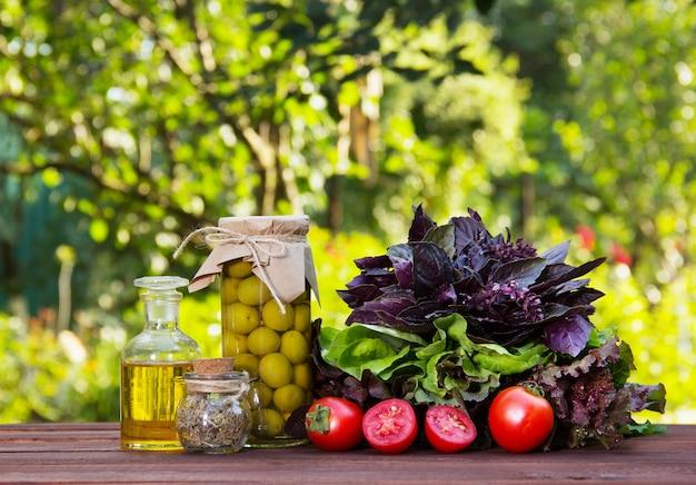 Ingredientes para a salada de verão, azeitonas, manjericão, tomate e azeite em cima da mesa