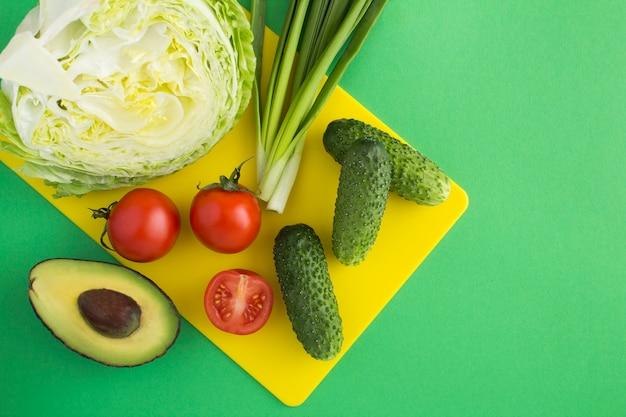 Ingredientes para a salada em uma placa de corte amarela no verde. vista superior.