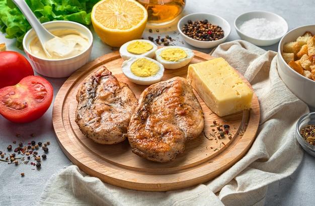 Ingredientes para a salada. peito de frango frito, queijo, ovos e ervas frescas em um fundo cinza. o conceito de alimentação saudável.