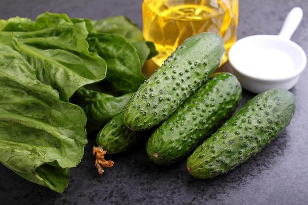Ingredientes para a salada: pepino, salada de alface romana, sal, óleo em um fundo preto
