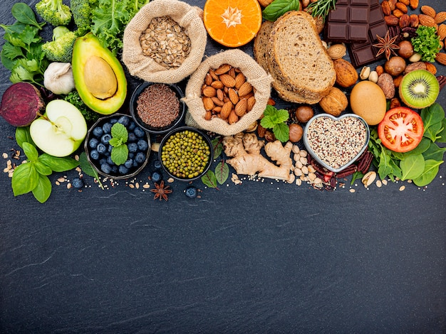 Ingredientes para a seleção de alimentos saudáveis. o conceito do alimento saudável setup no fundo de pedra escuro.